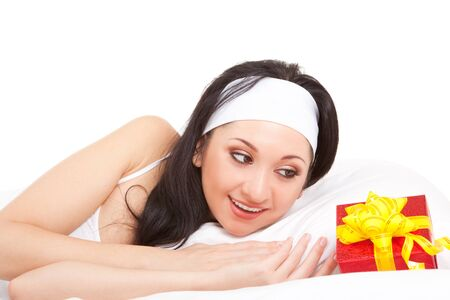 Cute woman on the white bed with gift box  photo