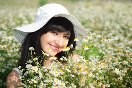 young happy girl in the chamomile field  photo