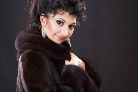 mink: Young fashion woman in fur coat on black background