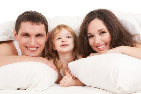 Happy family, mother, father and daughter resting on the white bed photo