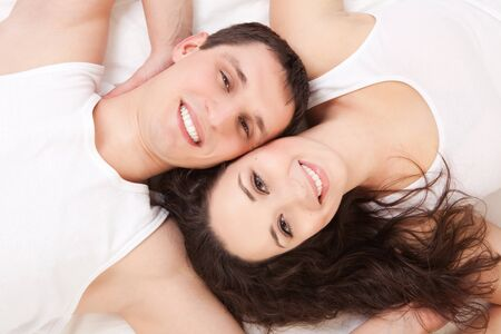 Young happy couple lying in the white bed  photo