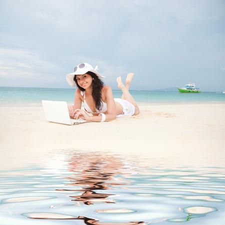 white  beach: Cute woman with white laptop on the summer beach