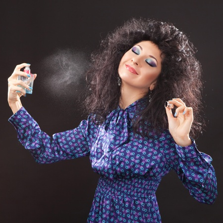 parfum: Young fashion woman with perfume on black background