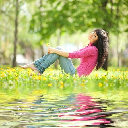 Hübsch Frau im Park mit Löwenzahn Standard-Bild