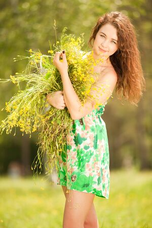 Young redhead woman in the park with flowers Stock Photo - 9827257