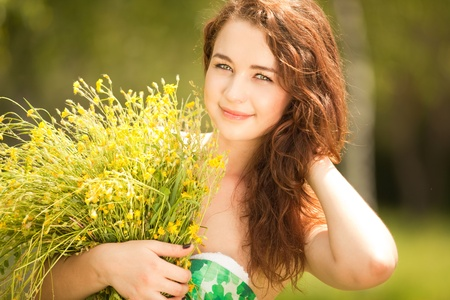 Young redhead woman in the park with flowers Stock Photo - 9827258