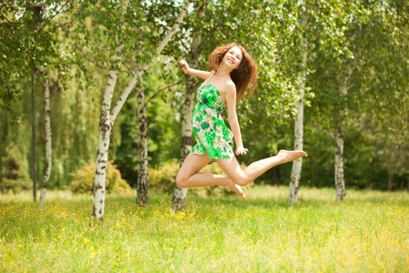 Young redhead woman jumping in the park with flowers Stock Photo - 9827256