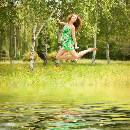 Young redhead woman jumping in the park with flowers Stock Photo - 10056238