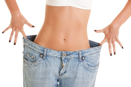 Funny woman shows her weight loss by wearing an old jeans, isolated on white background photo