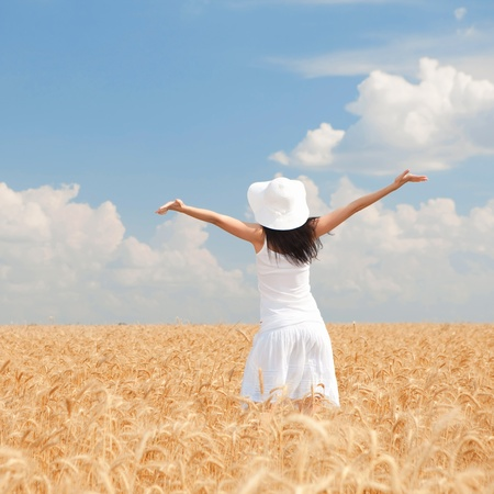 hands behind back: Happy woman in golden wheat
