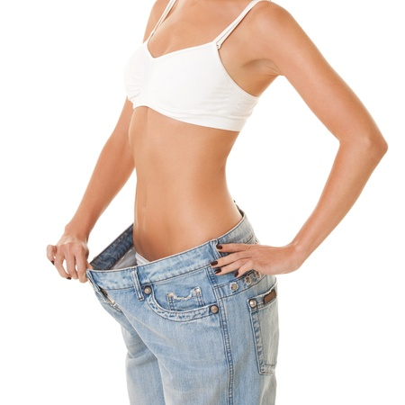 lose weight: Woman shows her weight loss by wearing an old jeans, isolated on white background
