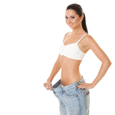 Pretty woman shows her weight loss by wearing an old jeans, isolated on white background Stock Photo - 10707043