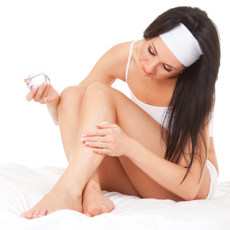 dry skin: Woman applying cream to her legs on the white background