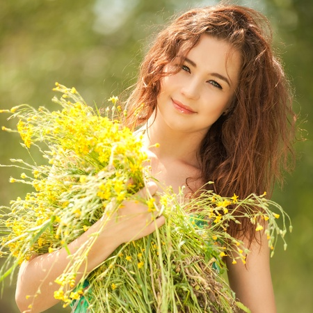 Young redhead woman in the park with flowers Imagens