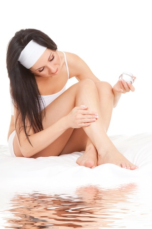 moisten: Woman applying cream to her legs on the white background