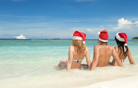 Happy friends in santa hats on the beach. Christmas vacation photo