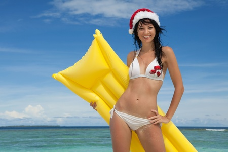 Happy santa woman with inflatable mattress on the beach. Christmas vacation photo