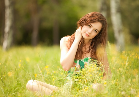 Young redhead woman in the park with flowers photo