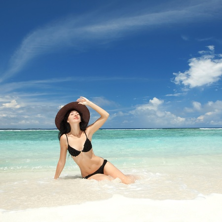 Happy fashion woman on the beach photo