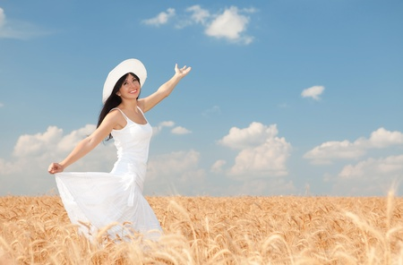 Young woman in the field of golden wheat photo