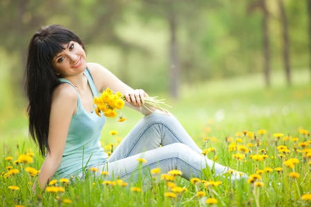 siting: Cute woman in the park with dandelions