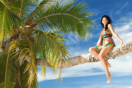 Fashion woman siting upon palm tree photo