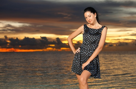 Fashion woman on the sea sunset background photo