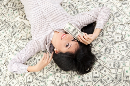 heap: Young business woman resting upon money