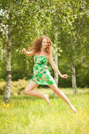 Young redhead woman jumping in the park with flowers photo