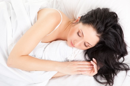Cute woman sleeping on the white bed photo