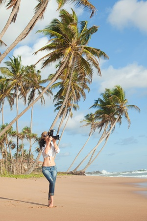 Fashion woman on tropical beach with photo camera photo