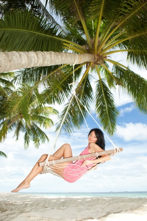 Happy woman relaxing in hammock on a tropical beach Stock Photo