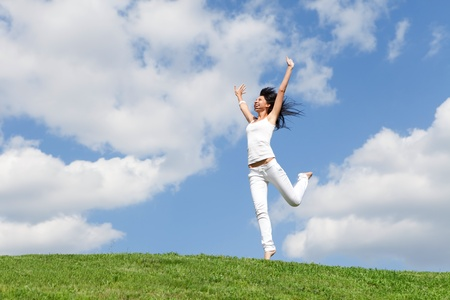 pretty young woman jumping on green grass photo