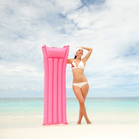 Happy woman with inflatable mattress on the beach Stock Photo - 13248194