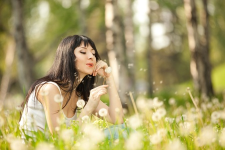 pollen: Cute woman in the park with dandelions