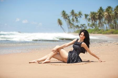 Fashion woman sitting on the beach photo