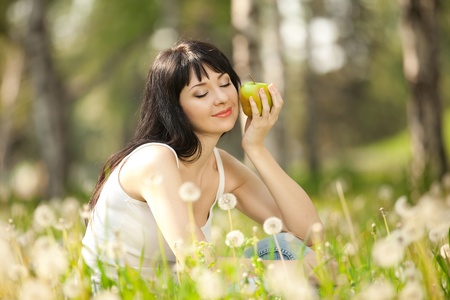 dandelion field: Cute woman eating the apple in the park with dandelions