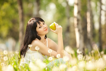 Cute woman eating the apple in the park with dandelions photo