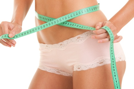 Athletic woman body with measure tape photo