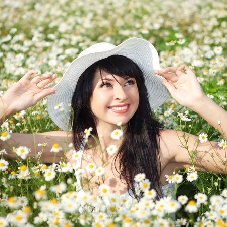 Young happy woman in the daisy field photo