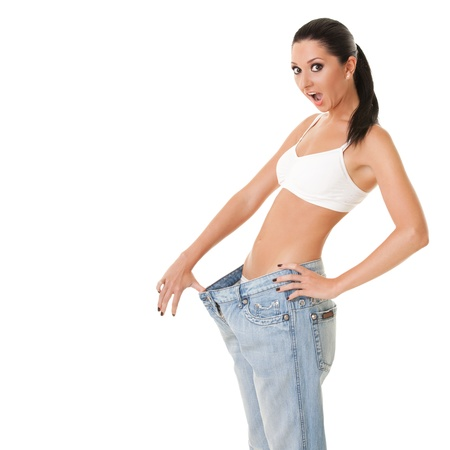 weight loss success: Pretty woman shows her weight loss by wearing an old jeans, isolated on white background Stock Photo