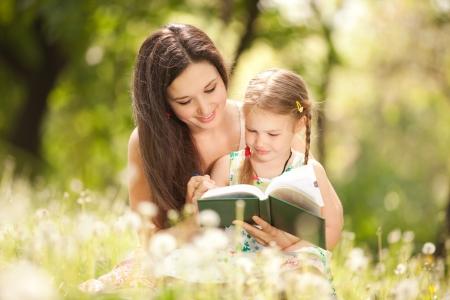 niños leyendo: Madre con hija en el parque Foto de archivo