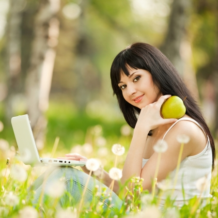 Cute woman with white laptop in the park with dandelions photo