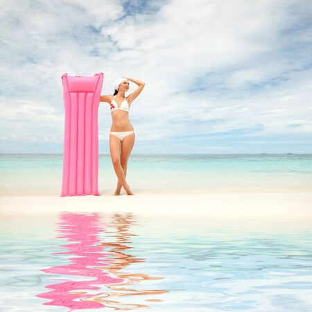 Happy woman with inflatable mattress on the beach photo