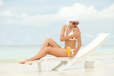 Young woman with sun-protection cream on the beach photo