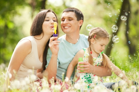 blowing bubbles: Happy mother, father and daughter blowing bubbles in the park Stock Photo