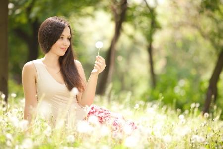 al�rgico: Mujer de lindo en el parque con los dientes de le�n Foto de archivo