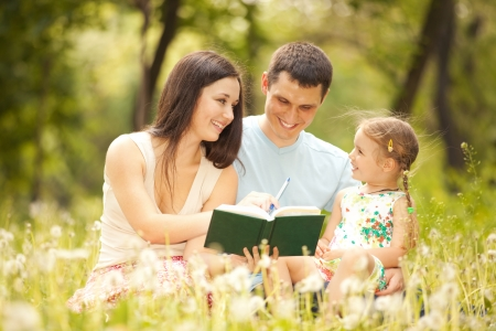 kid reading: Happy mother, father and daughter read a book in the park