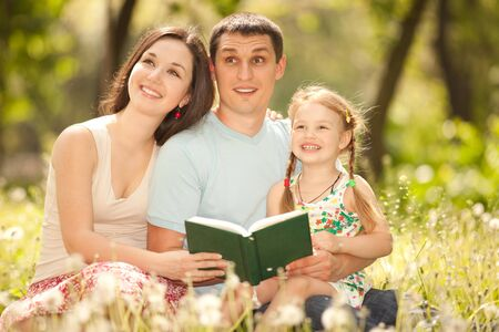 Happy mother, father and daughter read a book in the park photo