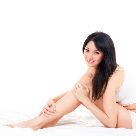 piedi nudi di bambine: Carino donna seduta sul letto bianco